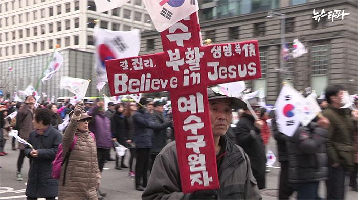 지난 삼일절에 열린 탄핵반대집회 현장에서 십자가를 든 참가자